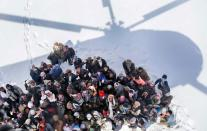 epaselect epa04641146 Survivors of an avalanche wait to receive relief goods distributed by an Army helicopter in Paryan district of Panjshir province, Afghanistan, 28 February 2015. According to local officials rescue teams restarted operations to find the victims of avalanches in Afghanistan's north-east as the total bodies found to at least 184 bodies in different areas of Panjsher province, with the total overall casualties at least 233 in various avalanche affected areas. EPA/HEDAYATULLAH AMID